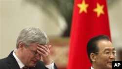 Canadian Prime Minister Stephen Harper, left, rubs his forehead while walking with Chinese Premier Wen Jiabao during a welcoming ceremony at the Great Hall of the People in Beijing Wednesday, Feb. 8, 2012. (AP Photo/Alexander F. Yuan)