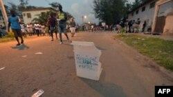 Les habitants passent devant un bulletin de vote dans une rue après que des personnes non identifiées aient endommagé un bureau de vote à Grand Bassam, le 16 décembre 2018, lors d'élections municipales et régionales partielles.