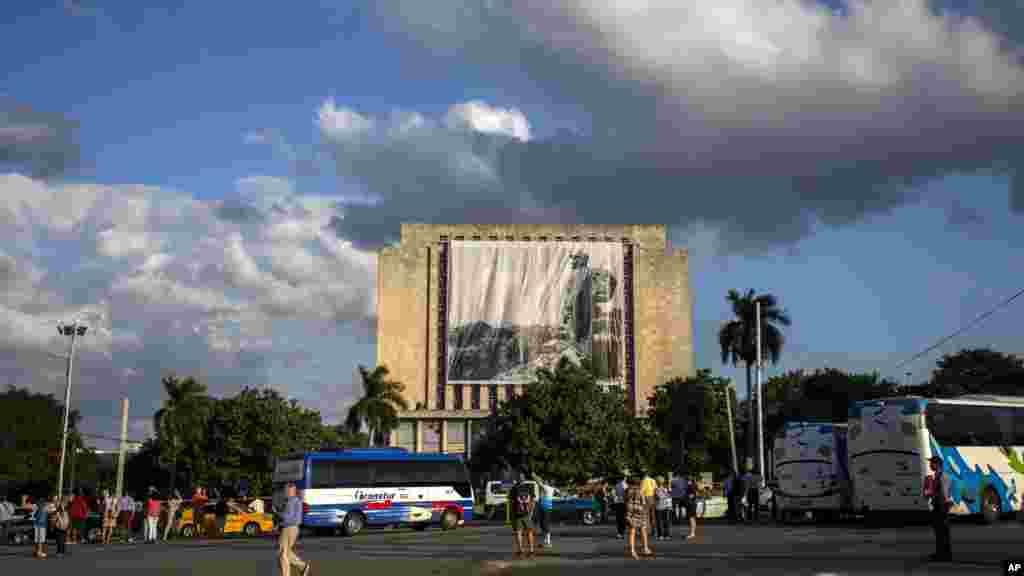 Les touristes devant la Place de la Révolution alors que les travailleurs accrochent une bannière du défunt Fidel Castro, le 27 novembre 2016.