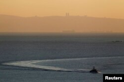 FILE - An Israeli naval vessel sails in the Mediterranean sea near the border with Lebanon, as Mount Carmel and the Israeli city of Haifa are seen in the background, Dec. 16, 2013.