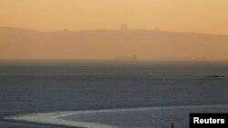 Sebuah kapal angkatan laut Israel berlayar di laut Mediterania dekat perbatasan dengan Lebanon, seperti Gunung Karmel dan kota Haifa di Israel terlihat di latar belakang, 16 Desember 2013. (Foto: Reuters)