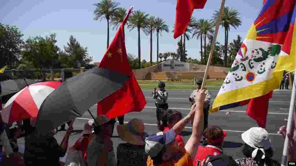 歡迎與抗議旗幟並列