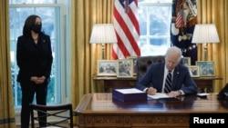 """Presidenti Joe Biden nënshkruan """"Planin Amerikan të Shpëtimit"""", ndërsa në krah qëndron Nënpresidentja Kamala Harris (Zyra Ovale, 11 mars 2021)"""