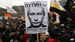 "Opposition supporters hold a rally to protest against violations at the parliamentary elections and the policies conducted by current Russian authorities in St. Petersburg. The sign reads, ""Putin, you are the traitor,"" December 18, 2011."