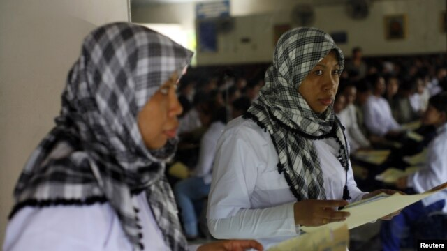 A Indonesian migrant worker heading for Middle East countries holds her passport documents at an immigration office.