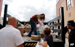 A member of the Red Cross unloads a truck of donations to waiting volunteers outside the Parthum School in Lawrence, Mass, Sept. 14, 2018.
