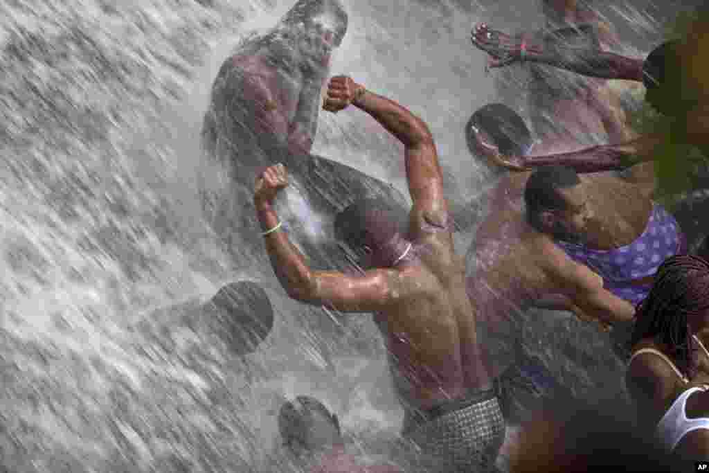 Người hành hương tắm dưới một thác được cho là có phép thanh tẩy trong lễ Nhảy Nước hàng năm ở Haiti, ngày 16 tháng 7, 2014.
