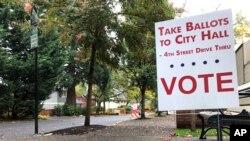 Sebuah plang di tepi jalan mengarahkan para pemilih ke depan sebuah perpustakaan di Lake Oswego, Ore., Rabu, 31 Oktober 2018 (foto: AP Photo/Gillian Flaccus)