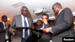 South Sudan's leader of the government's delegation Nhial Deng Nhial (L) exchanges a signed ceasefire agreement with the head of the rebel delegation Gen. Taban Deng Gai (R).