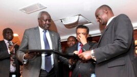 South Sudan's leader of the government's delegation Nhial Deng Nhial (L) exchanges a signed ceasefire agreement with the head of the rebel delegation Gen. Taban Deng Gai (R) to end more than five weeks of fighting.