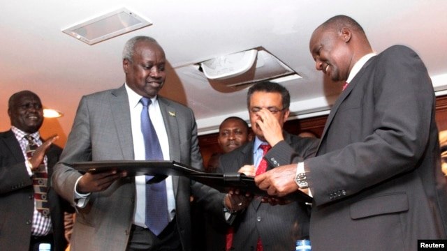 South Sudan's leader of the government's delegation Nhial Deng Nhial (L) exchanges a signed ceasefire agreement with the head of the rebel delegation Gen. Taban Deng Gai (R) to end more than five weeks of fighting after negotiations in Ethiopia's capital
