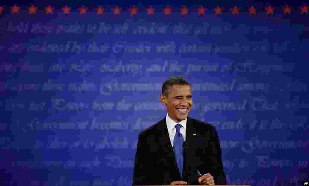 President Barack Obama smiles at moderator Jim Lehrer during the first presidential debate with Republican presidential nominee Mitt Romney at the University of Denver.