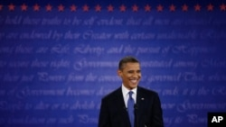 President Barack Obama smiles at moderator Jim Lehrer during the first presidential debate at the University of Denver, Oct. 3, 2012.