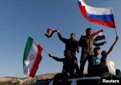Sirijci mašu iranskim, ruskim i sirijskim zastavama tokom protesta protiv vazdušnih napada koje predvode SAD, u Damasku, Sirija, 18. aprila 2018.