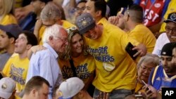 Democratic presidential candidate Sen. Bernie Sanders, left, has his photo taken with fans at the NBA basketball Western Conference finals between the Golden State Warriors and the Oklahoma City Thunder in Oakland, California, May 30, 2016.