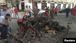 Para anggota militer dan warga mengerumuni mobil yang hancur setelah meledak di dekat perkantoran polisi militer di Tripoli (4/8).