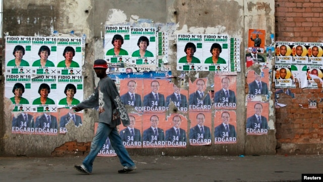 A man walks past campaign posters outside a polling center in the capital Antananarivo, Oct. 25, 2013.