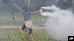 یکی از مهاجران، کپسول گاز اشک آور را به سمت پلیس مقدونیه پرتاب می کند - ۲۲ فروردین ۱۳۹۵