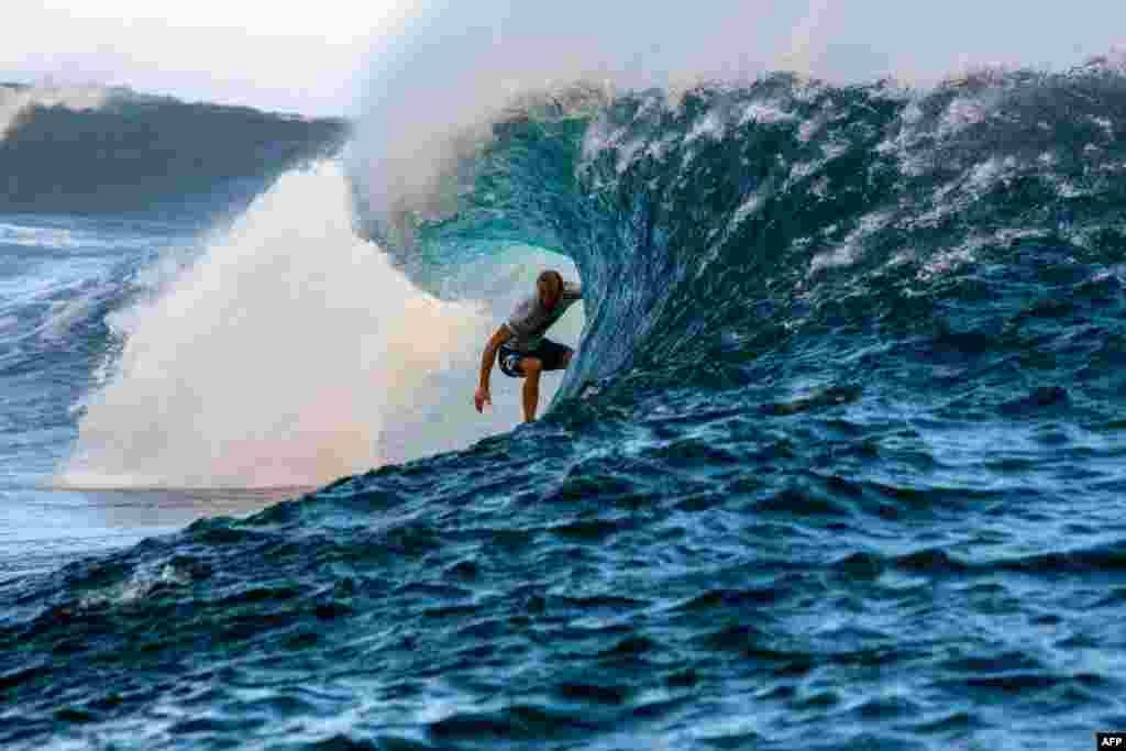 លោក Owen Wright កីឡាករអូស្ត្រាលីកំពុងប្រកួតនៅក្នុងព្រឹត្តិការណ៍កីឡាជិះក្តាររំអិលលើទឹក Billabong Pro Tahiti, World Surf League ២០១៥ នៅតាមបណ្តោយឆ្នេរក្នុងភូមិ Teahupo'o ភាគខាងលិចកោះ Tahiti នៃប្រជុំកោះ French Polynesia កាលពីថ្ងៃទី ២៤ ខែសីហាឆ្នាំ ២០១៥។