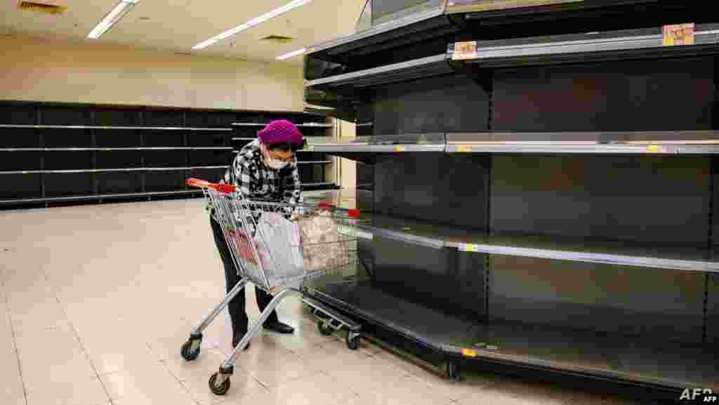 홍콩의 식료품점에서 신종 코로나바이러스 감염을 막기 위해 마스크를 착용한 여성이 텅텅 비어 있는 진열대 옆에서 카트 내 물건들을 정리하고 있다.