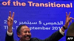 Sudanese Prime Minister Abdalla Hamdok flashes the victory gesture during a press conference unveiling the first cabinet since veteran leader Omar al-Bashir's overthrow, in Khartoum, Sept. 5, 2019.