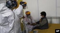 Un médico revisa los signos vitales de una anciana luego de ser inoculada con una dosis de la vacuna Pfizer COVID-19 como parte del período de observación, en el centro de convenciones convertido en sitio de vacunación, en Quito, Ecuador, el 31 de marzo.