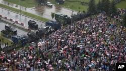 在白俄罗斯首都明斯克,反对派支持者面对警察封锁线走向总统卢卡申科的官邸和平宫。(2020年8月30日)