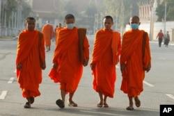 Buddhist monks wear masks as they walk near Royal Palace in Phnom Penh, Cambodia, Jan. 28, 2020.