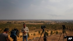 FILE - TV journalists work on a hilltop in Ceylanpinar, Sanliurfa province, southeastern Turkey, as in the background smoke billows from a fire in Ras al-Ayn, Syria, Oct. 20, 2019.