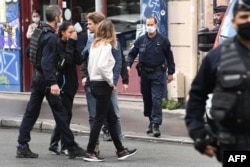 A woman reacts after several people were injured near the former offices of the French satirical magazine 'Charlie Hebdo' following an attack by a man wielding a knife in Paris, Sept. 25, 2020.