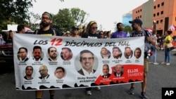 Manifestantes sostienen una pancarta con los rostros del gobernador Ricardo Rosselló (al centro), que ha anunciado su renuncia, y las de otros políticos, en San Juan, Puerto Rico, el lunes 29 de julio de 2019. (AP Foto/Brandon Cruz González)