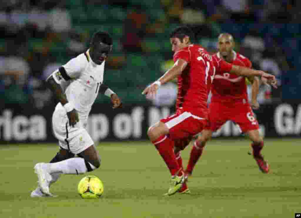 Ghana's Sulley Muntari (L) is challenged by Tunisia's Mejdi Traoui during their African Nations Cup quarter-final soccer match at Franceville stadium February 5, 2012.