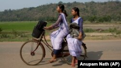 Indian girls go to a school on a bicycle at Roja Mayong village about 40 kilometers (25 miles) east of Gauhati, India.