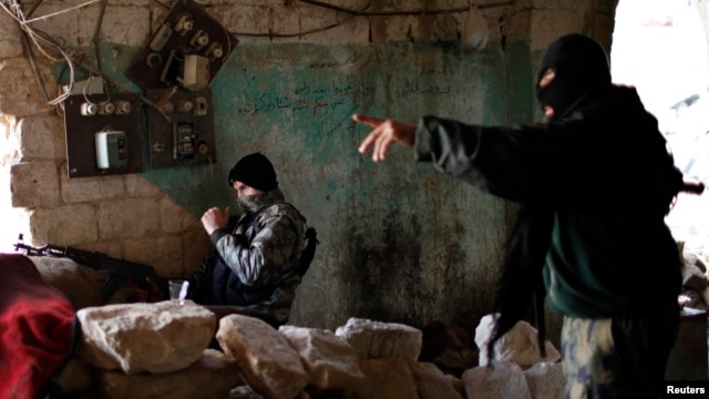 Jihadist fighters from the Jabhat al-Nusra group take up positions in Aleppo during a battle against Syrian government forces December 24,2012. Al-Nusra fighters are also accused of clashes with other anti-government rebels.