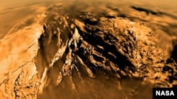 FILE - Titan is seen from the Huygens probe as it descended to the surface in 2005.