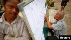 Seorang pria memeriksa daftar pemberi suara di TPS wilayah Phnom Penh(27/7).