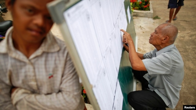 A man checks voter lists at a polling station in a Phnom Penh suburb July 27, 2013.