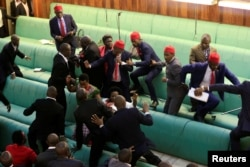 FILE - Ugandan opposition lawmakers fight with plainclothes security personnel in the parliament while protesting a plan to remove the 75-year age limit for the presidency, in Kampala, Sept. 27, 2017.