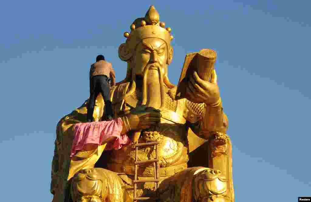 چین میں ایک کاریگر تاریخی مجسمے کی مرمت کر رہا ہے۔