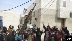 In this Sunday, April 1, 2012 photo, Syrians chant slogans against President Bashar Assad upon the arrival of the Free Syrian Army in a neighborhood of Damascus, Syria. Government and opposition forces clashed across Syria Monday as international envoy Ko