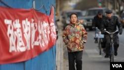 Seorang perempuan berjalan melewati bagian depan sebuah penjara di Beijing tempat di mana Liu Xiaobo.