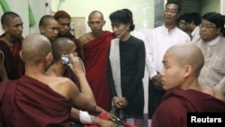 Burmese pro-democracy leader Aung San Suu Kyi visits Buddhist monks, wounded in a police crackdown on activists fighting a Chinese copper mine project, at a hospital in Monywa, Nov. 29, 2012.