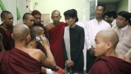 Aung San Suu Kyi visits Buddhists monks wounded in police crackdown on protests against a copper mine project, Nov. 2012.