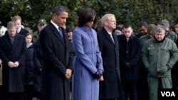 El presidente Barack Obama, la primera dama, Michelle Obama y miembros del equipo de los congresistas durante el minuto de silencio en el Capitolio.