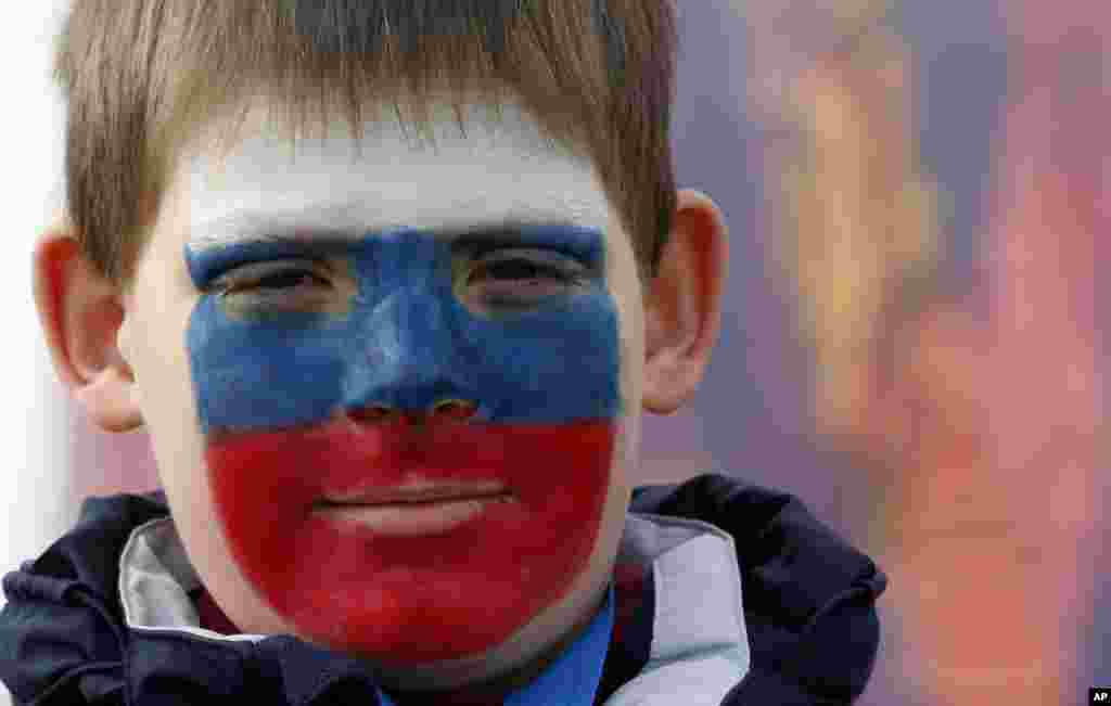 Limonov Egor Dmitrievich wears face paint in the colors of the Russian flag at the 2014 Winter Olympics in Sochi, Russia.