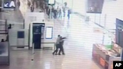 In this image taken from video of CCTV footage provided to AP on the condition that its source not be revealed, suspected Islamic extremist Ziyed Ben Belgacem, center left, holds a soldier after grabbing her from behind at Paris' Orly airport, March 18, 2