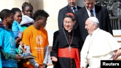 Pope Francis meets Cardinal Luis Antonio Tagle (C) and a group of migrants during the Wednesday general audience in Saint Peter's Square at the Vatican, Sept. 27, 2017.