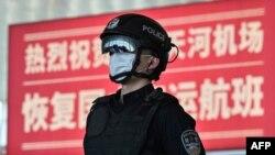 2020年4月8日武漢城市解封,天河國際機場內一名戴著口罩的警察站在標語牌前。