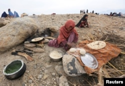 An internally displaced Afghan woman who fled from recent conflict cooks bread outside a shelter in Khogyani district of Nangarhar province, Afghanistan, Nov. 28, 2017.
