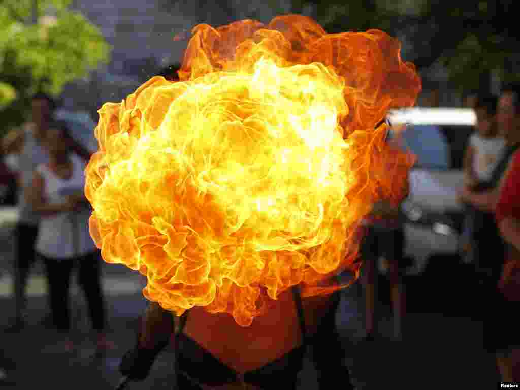 A street performer breathes fire on the eve of the feast day of the town's patron Saint Rita in Paranaque city, metro Manila, Philippines, May 17, 2014.